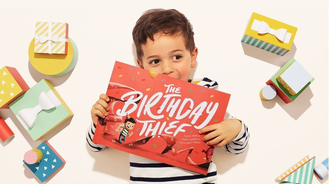A little boy holding his birthday thief book